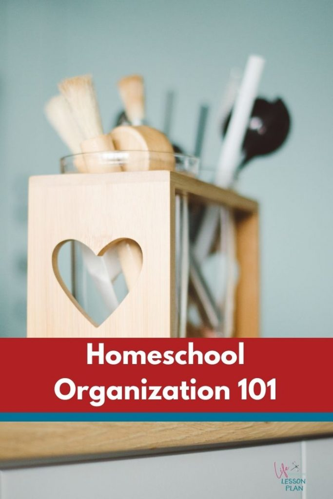 an organizer with a heart cut-out and pencils, pens, and art supplies